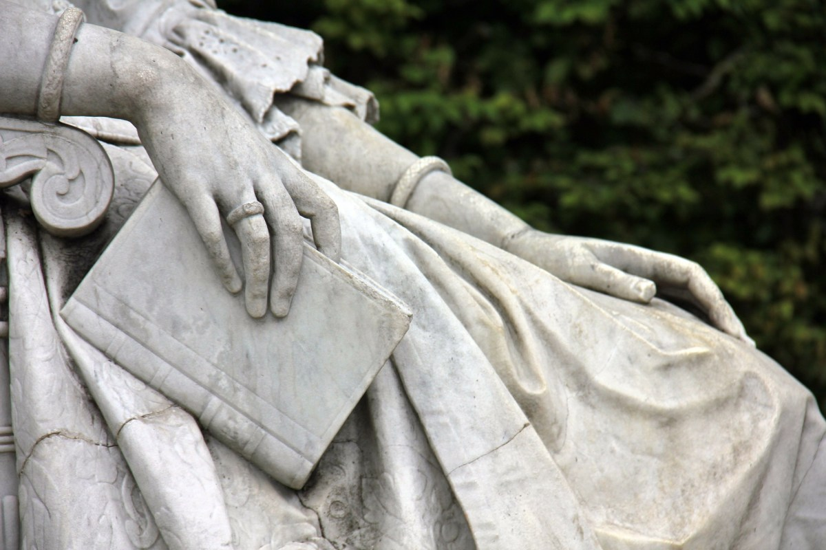 Statue hand holding a book
