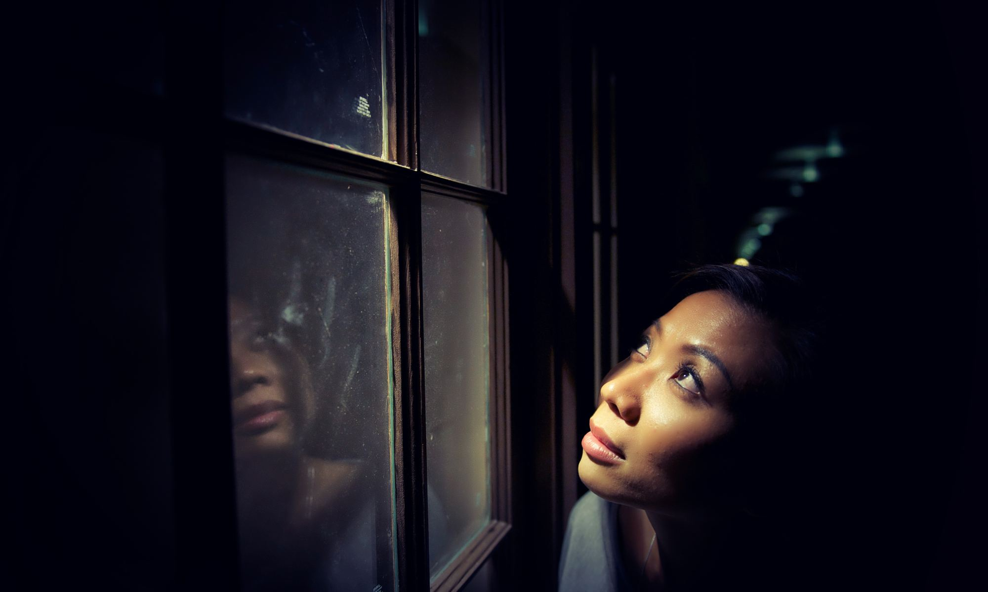 dark skin woman standing in front of window, looking up at the sky