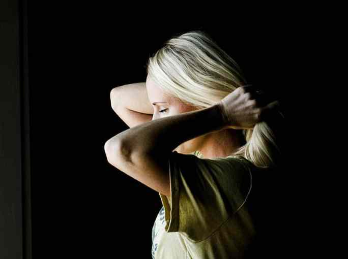 Woman holding her hair back in dark room