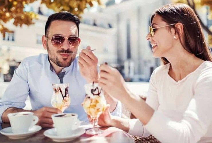 happy man and woman eating ice cream at cafe