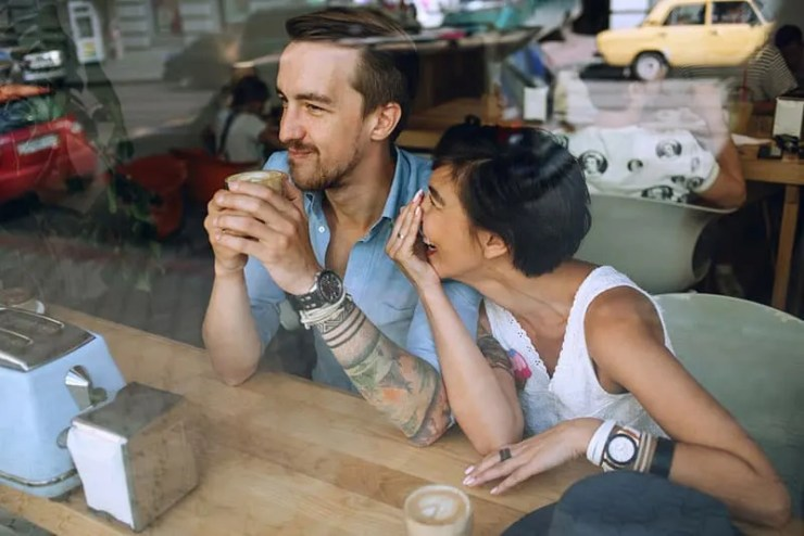 woman laughing at man while sitting at cafe