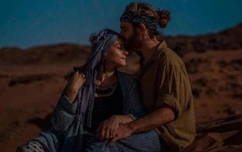 Man kissing woman on her forehead in a desert background in the evening