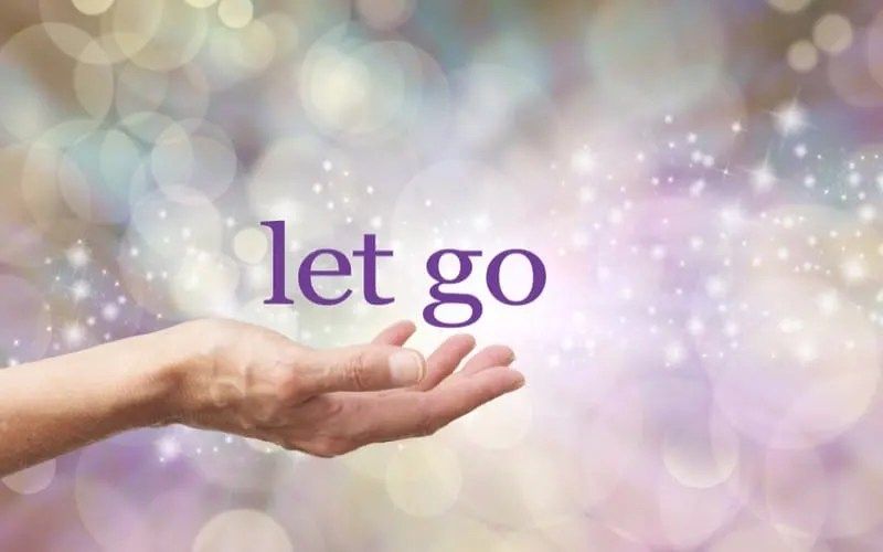 Female open hand with the words LET GO above against a sparkling background