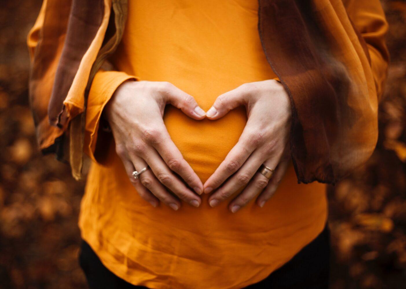 Het Gezinsleven - Moeder en Kind - Kinderwens - Stoppen met de pil - Vrouw vormt met haar handen een hart op haar buik
