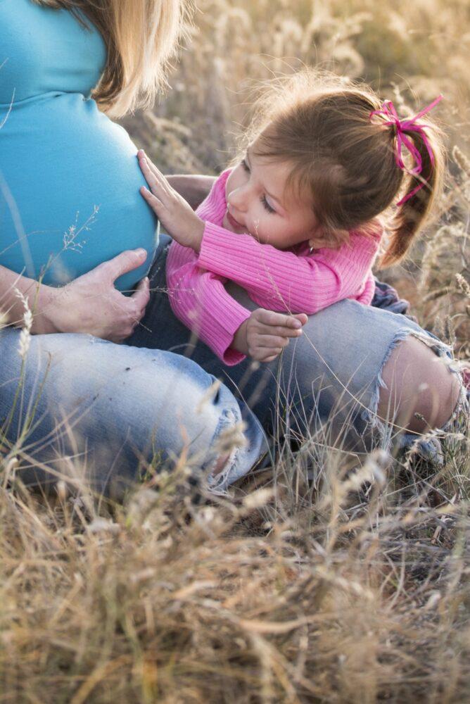 Het Gezinsleven - Moeder en Kind - Zwangerschap - Alles over bekkenpijn tijdens je zwangerschap - Kind aait de buik van haar zwangere moeder