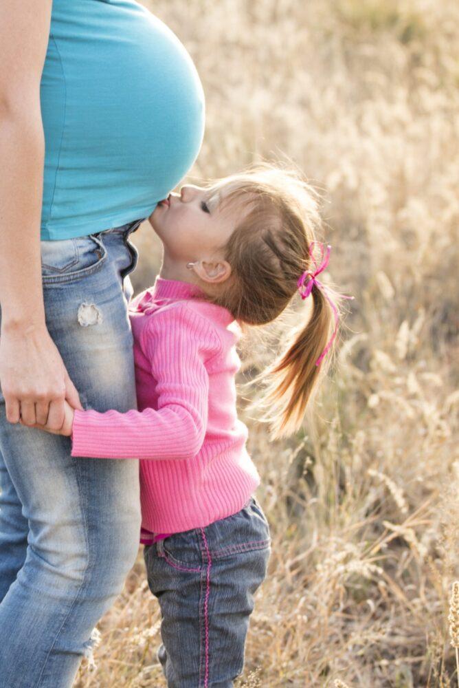 Het Gezinsleven - Moeder en Kind - Zwangerschap - Alles over bekkenpijn tijdens je zwangerschap - Kind kust de buik van haar zwangere moeder