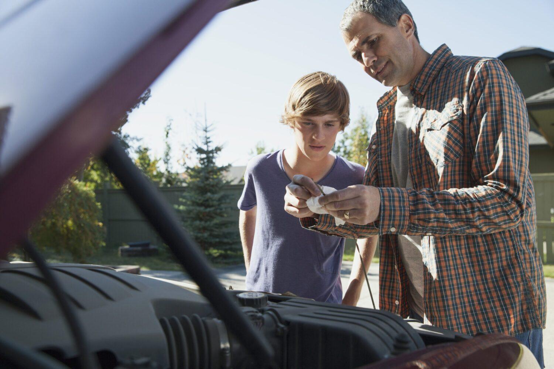 Het Gezinsleven - Vakantie - Autovakantie - Autovakantie met kinderen - Vader en zoon controleren het motor oliepeil