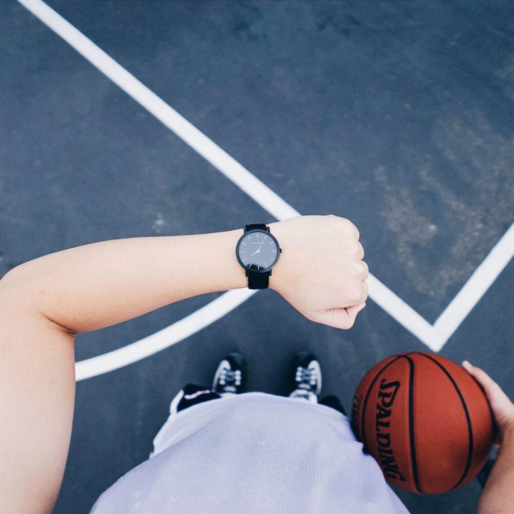 Het Gezinsleven - Lifestyle - Sporten - Drinken en eten voor het sporten, hoe zit het? - Jongen kijkt tijdens het basketballen op zijn horloge