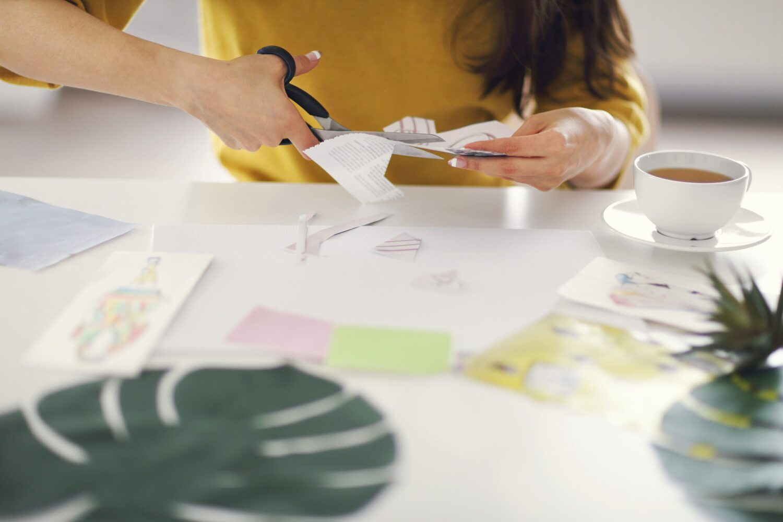 Het Gezinsleven - Lifestyle - Hobby's - Wil je jouw doelen bereiken? Maak een Vision Board! - Vrouw knipt afbeeldingen uit voor haar vision board