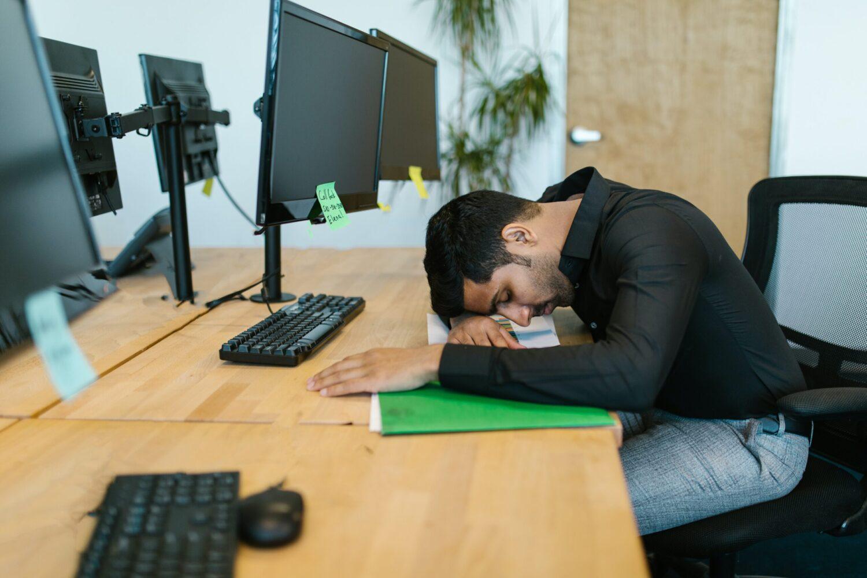 Het Gezinsleven - Lifestyle - Mindset - Tips voor de perfecte powernap - Man slaapt op het kantoor met hoofd op het bureau