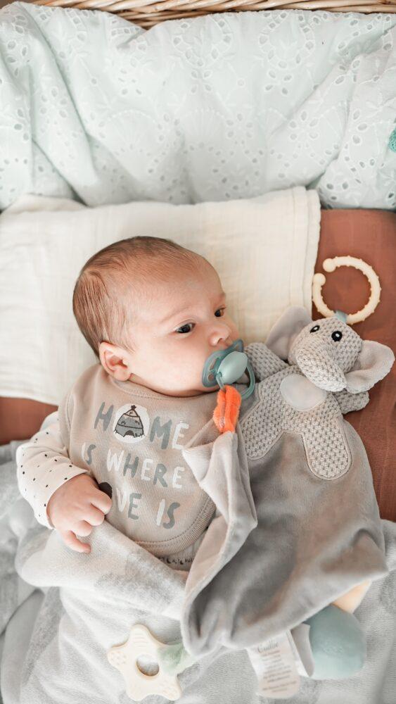 Het Gezinsleven - Moeder en Kind - Baby - Duimen of toch een fopspeen? - Baby in bed met fopspeen