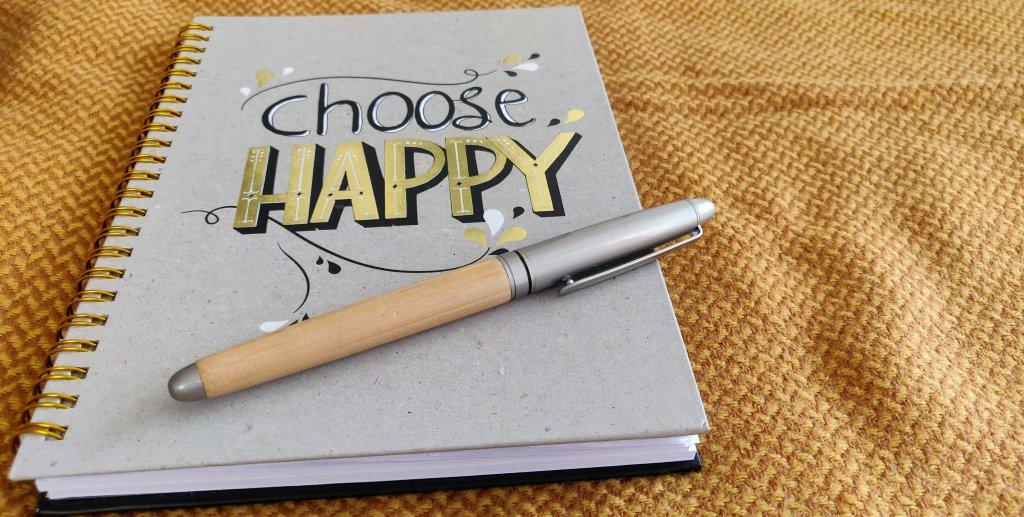 """Een gele achtergrond met daarop een notitieboekje. Op het notitieboekje staat de tekst """"Choose Happy""""."""