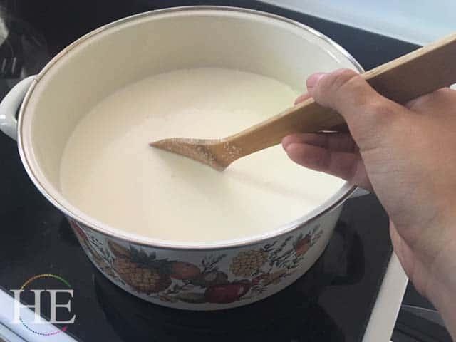 stirring a pot of hot milk to make ricotta cheese
