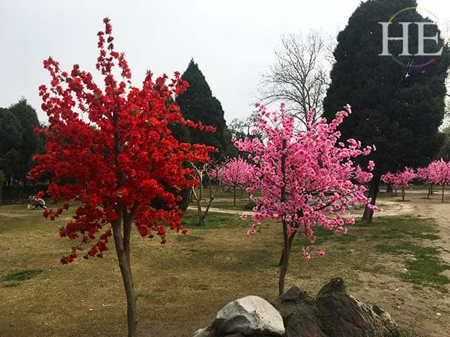 fabric flowers adorn a group of trees at a park in zhengzhou