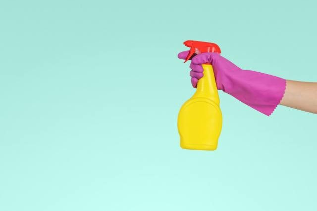 Gloved hand holding a cleaning supply