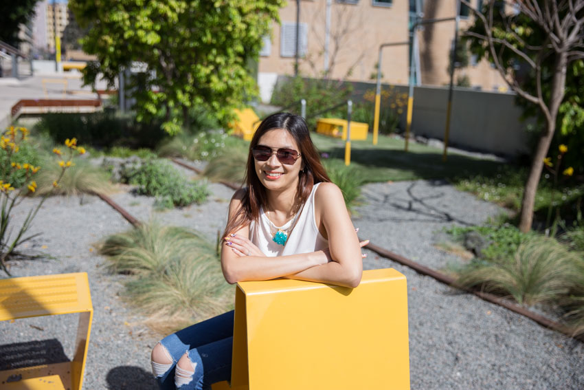 Me leaning over the edge of a yellow chair, with my sunglasses on