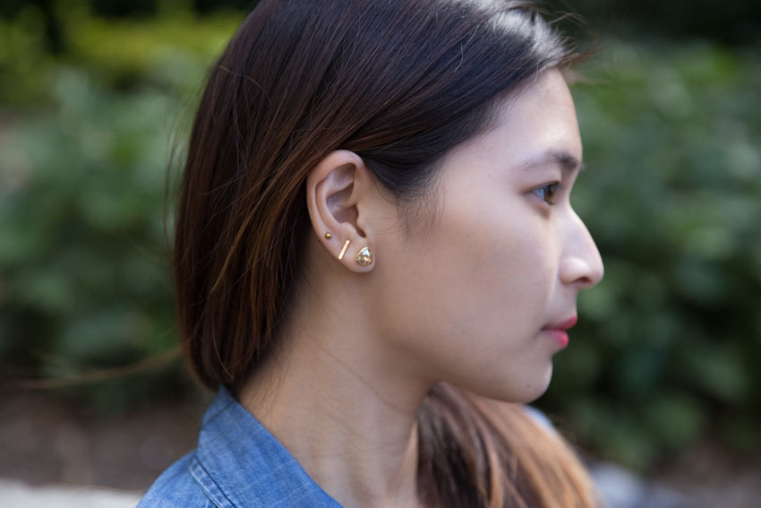 Close up of my small rose gold ball stud and bar stud earrings and my triangular gold earring with coloured stone