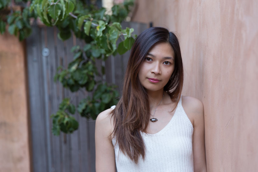 Close shot of me leaning against a brown-red wall with a wooden gate in the background
