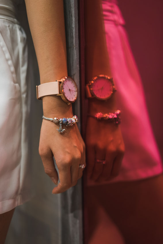 Close shot of my wrist with a Pandora bracelet and round-faced watch, against a red tinted mirror