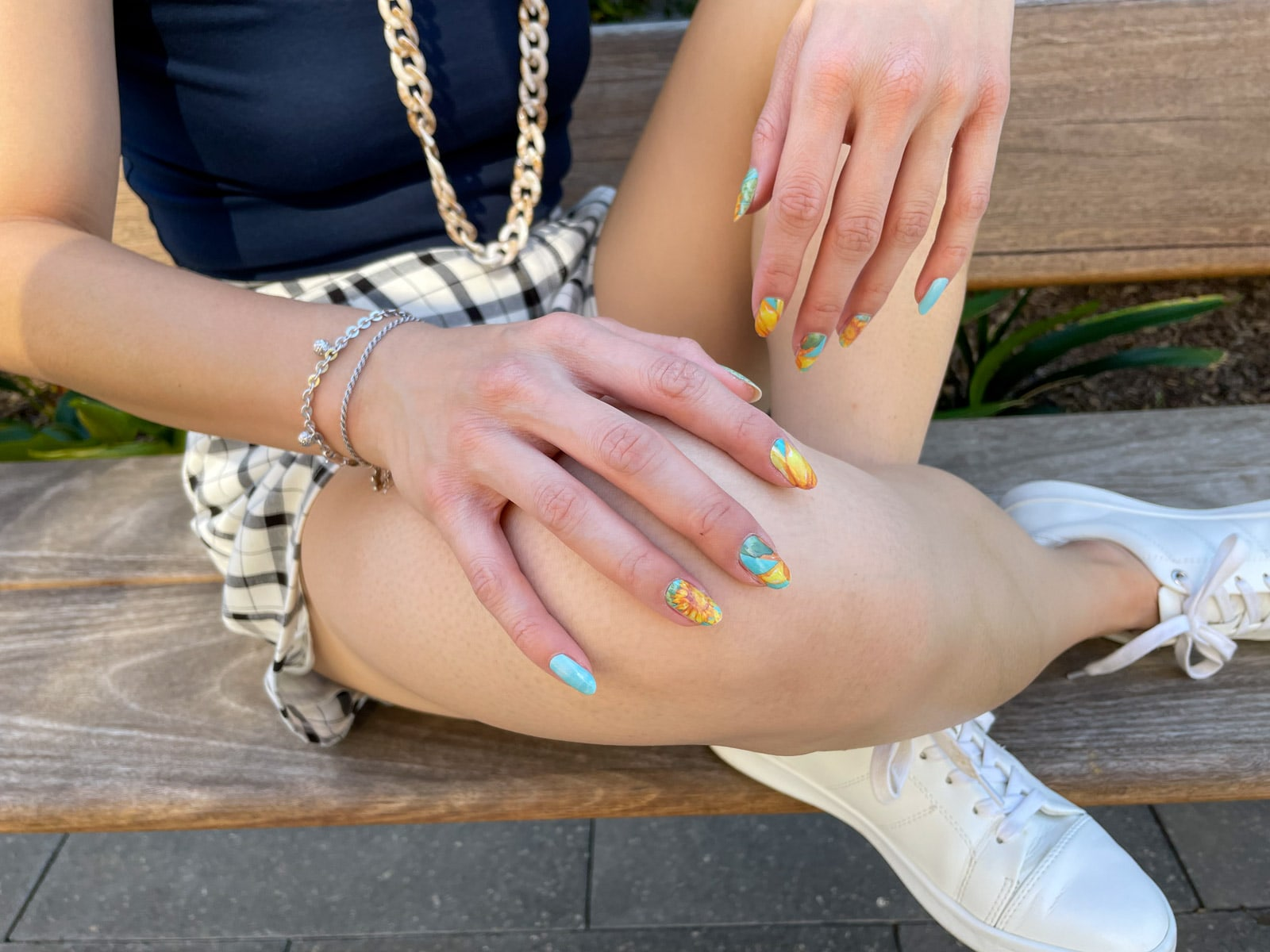 image 5: A close-up of the hands of the woman in image 1. She has yellow and sky blue nail art, resembling sunflowers. Her hands are resting on her knees and her legs are crossed.
