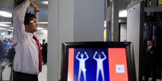 Image: Man in background inside full-body scanner with hands above his head while scanner image appears onscreen in foreground Photo: Gizmodo.com