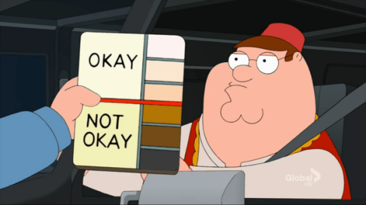 """Image: Family Guy character Peter Griffin sits in a car while the hand of a police officer holds a card denoting light skin tones as """"Okay"""" and dark skin tones as """"Not Okay"""" Photo: Family Guy"""