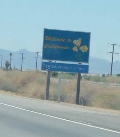 "sign on the side of the road reading: ""Welcome to California: Entering Pacific Time"""
