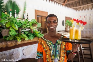 Fakihi serving drinks, dressed in a dashiki at Hakuna Majiwe in Paje, Zanzibar | @dipyourtoesin
