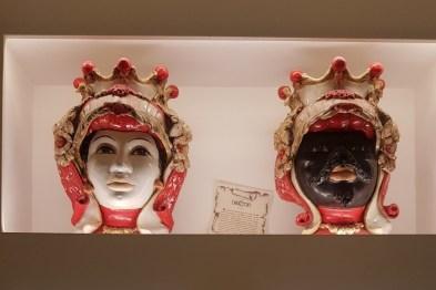 Vintage Sicilian masks perched upon a shelf at Tasting Sicily