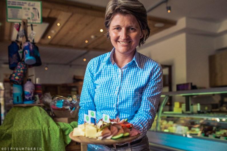 Eva Rainer in Dorfladen presenting organic food cafe in Leogang, Austria