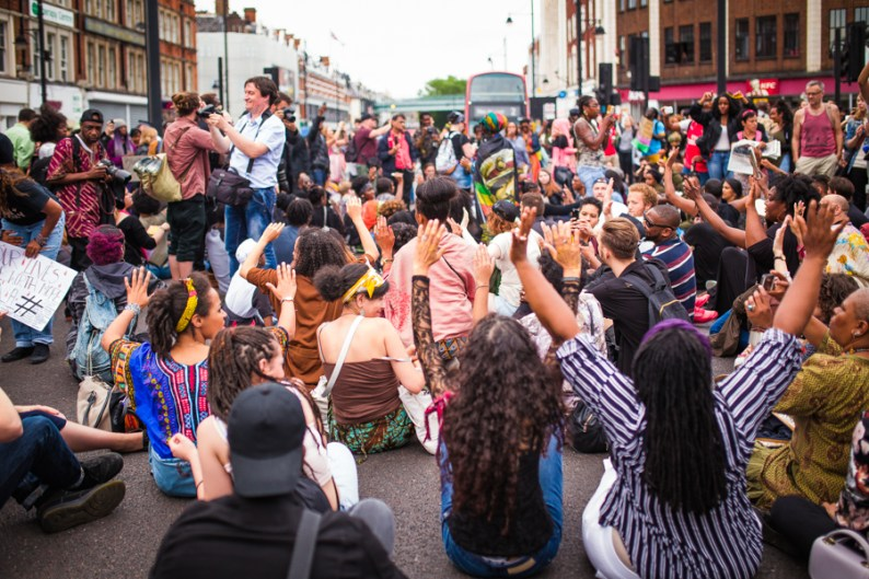 "More protesters sitting on the road with ""Hands Up! Don't Shoot"" posture 