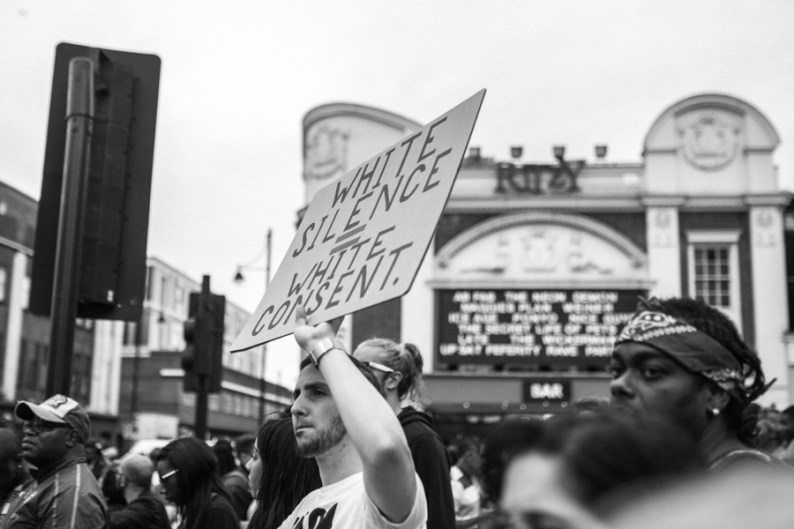 White protester holding up sign captioned: White Silence = White Consent | Black Lives Matter protest, London | Be An Ally to Black People