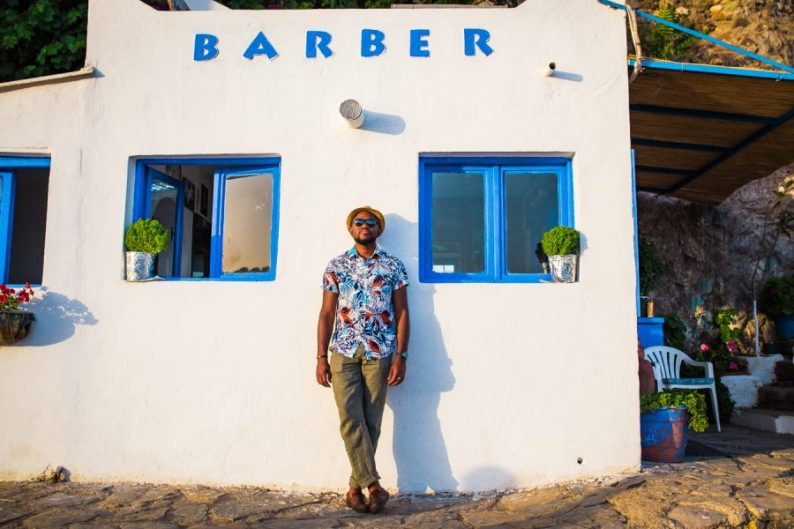 Omo in a Hawaiian shirt, wearing a hat, leaning against a white wall underneath a large sign saying Barber | Turkey