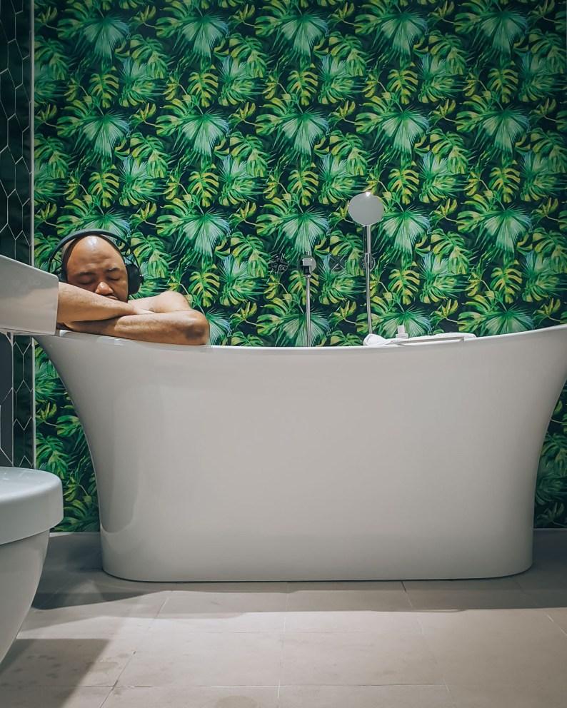 Bathtub in Hotel Indigo, Bath, Somerset | Bathroom has forest decor | Man soaking in tub is listening to music from his headphones