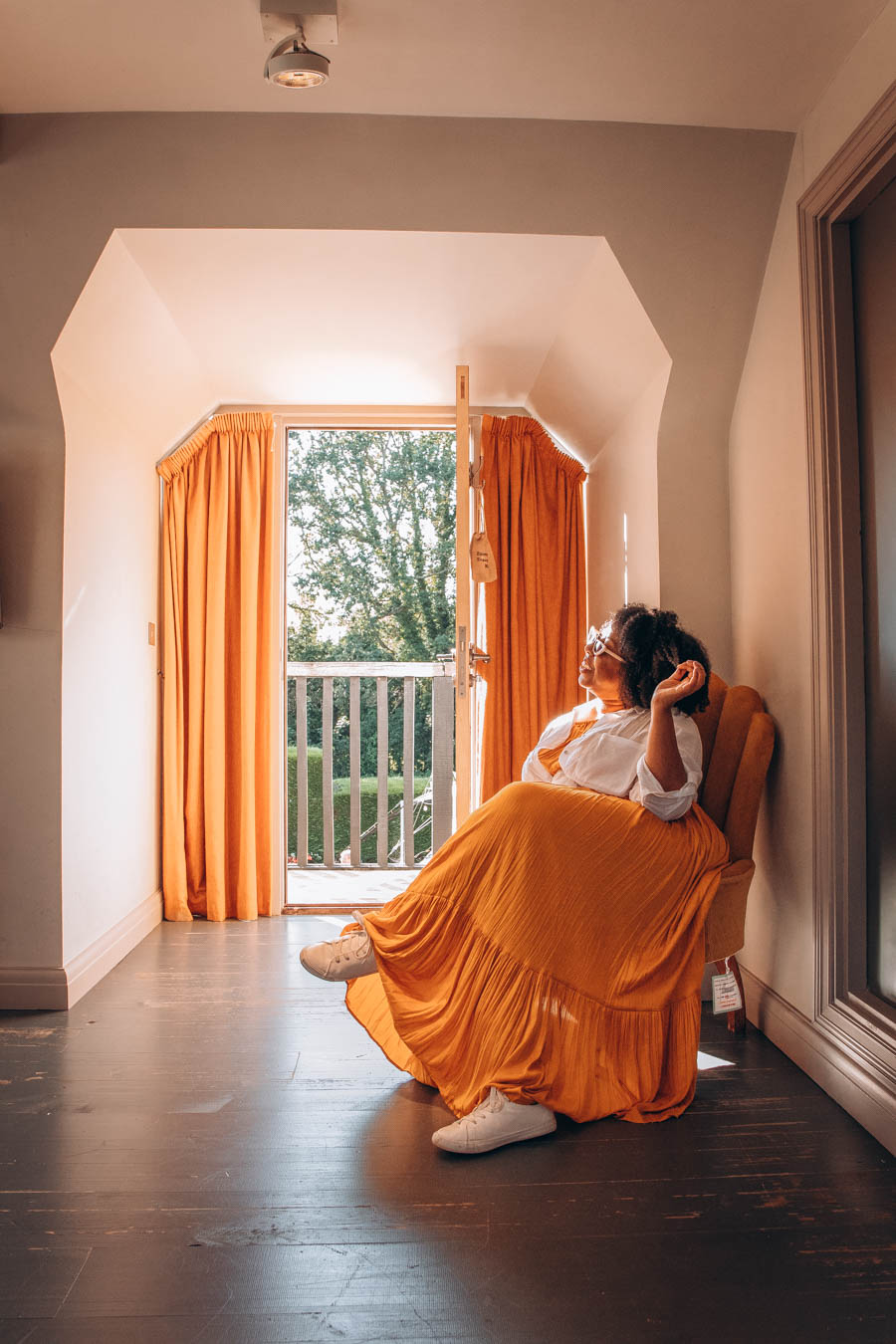 Eulanda wearing orange skirt sitting in doorway of room at The Old House Inn, Copthorne   West Sussex