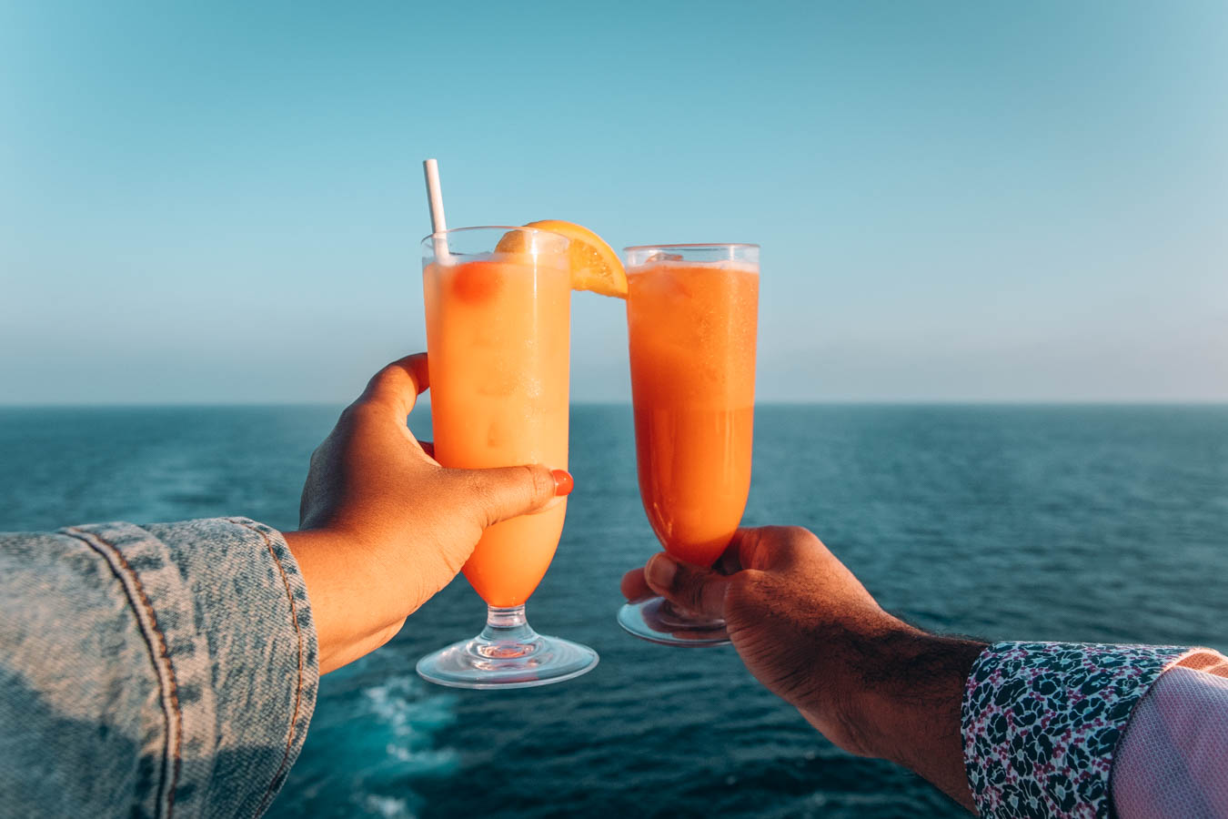Two hands holding cocktails facing the horizon, sunset view from deck of Sky Princess