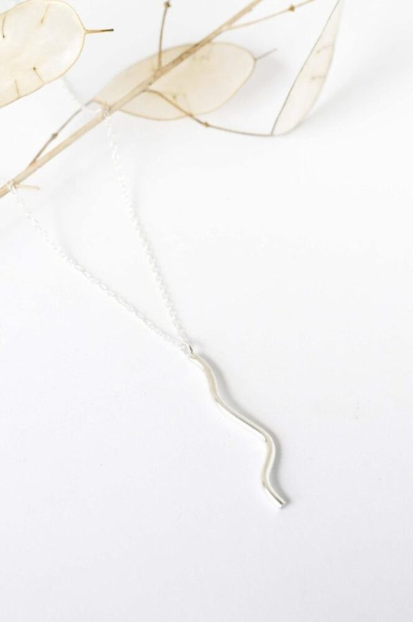 Ethically-handmade Feels Curvy Silver Necklace on a white background.