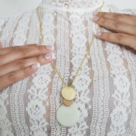 Woman wearing the overlapping tagua disc pendant and chain necklace over a white top.