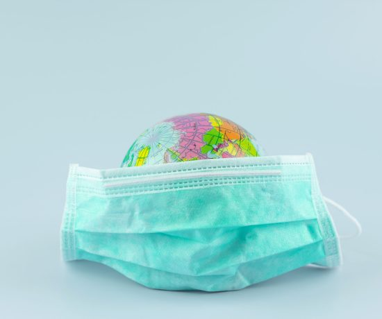 COVID-Safe Travel | Globe of the world wearing a mask on a light blue background