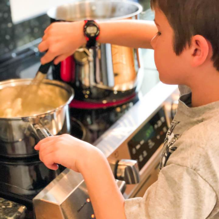 young boy stirring a pot on the stove