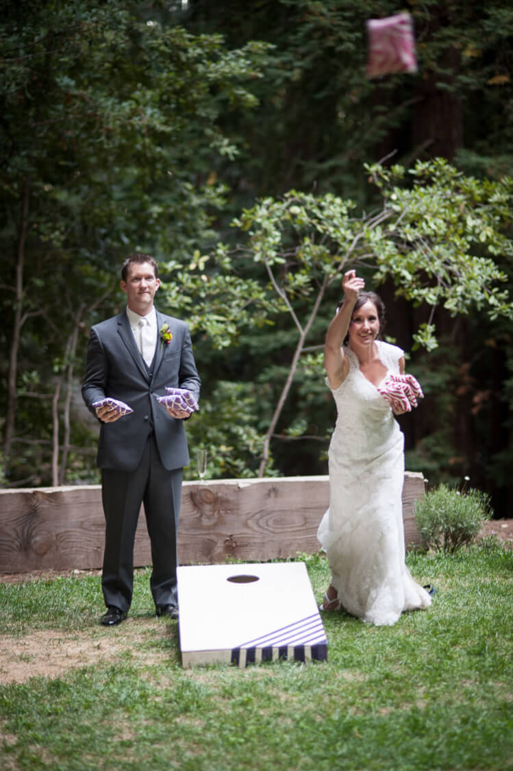 bride and groom playing cornhole game on wedding day