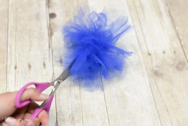 scissors separating blue tulle to make poofy firework look