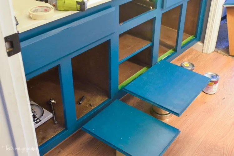 blue cabinets with doors and drawers off