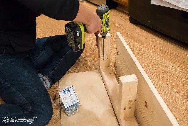 man drilling holes in wooden pieces