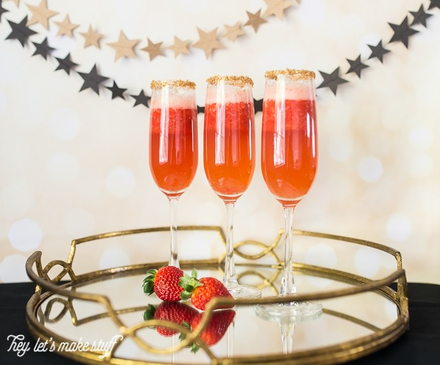 red strawberry champagne flutes on serving platter