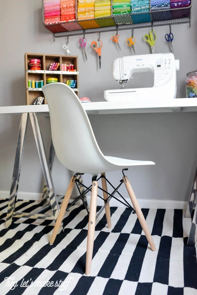 desk in craft room with black and white rug, white chair, and sewing machine on table