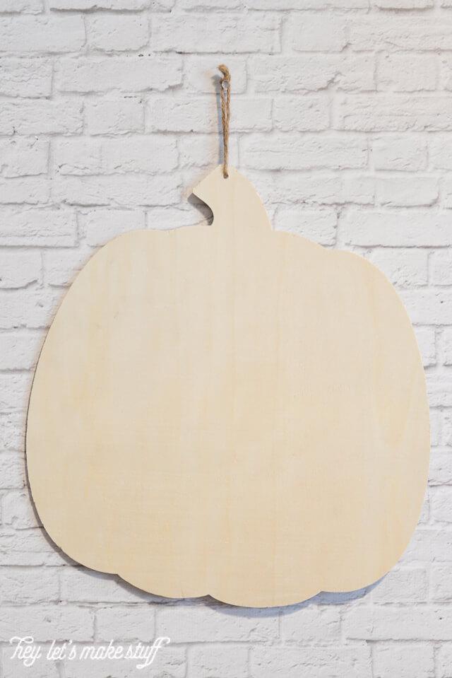 wooden pumpkin cutout hung on white brick wall