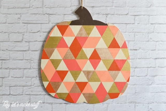 finished painted geometric pumpkin hung on white brick wall