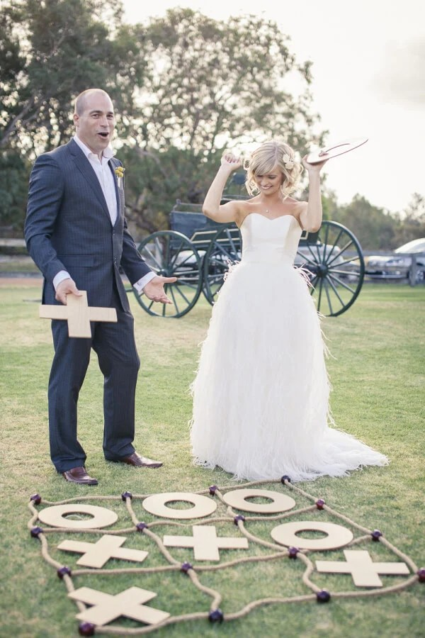 outdoor wedding games - Bride and groom playing Tic Tac Toe