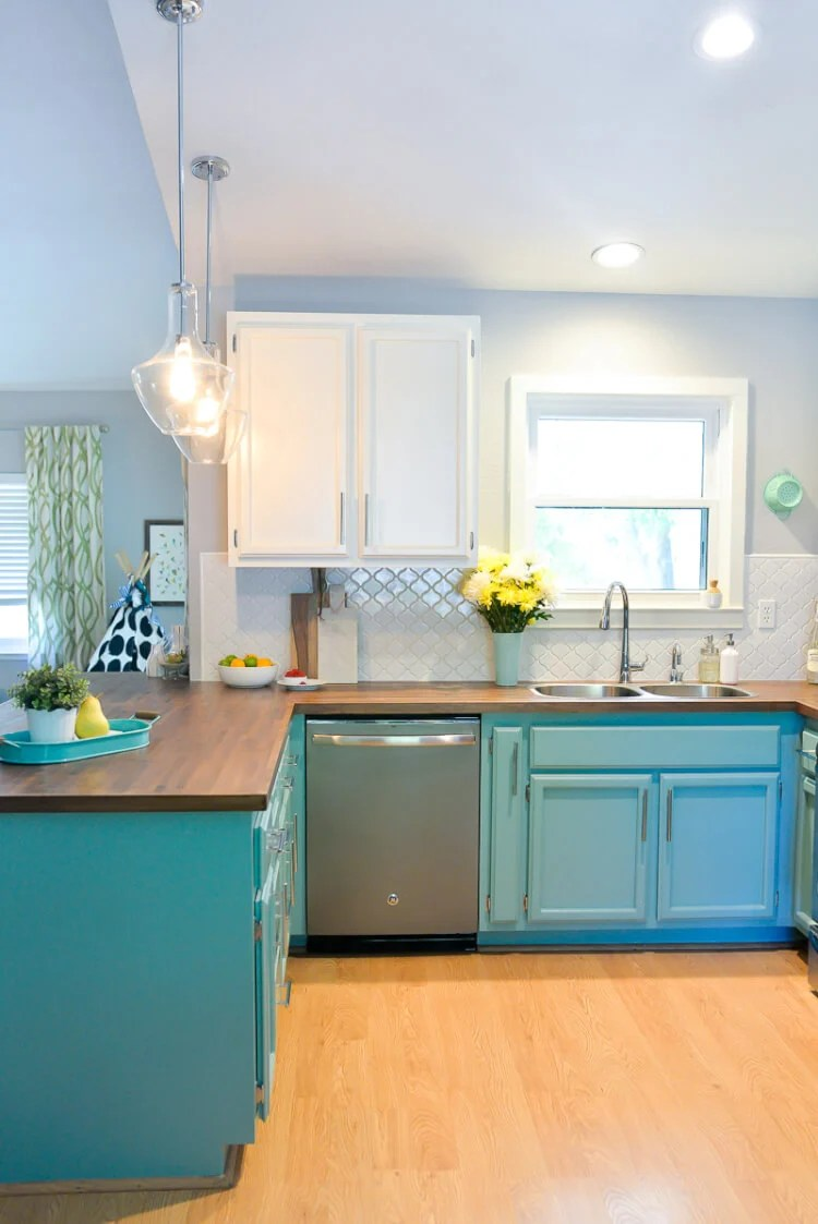 1980's kitchen with bright painted cabinets, new lighting, and gorgeous butcher block countertops.